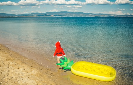 New year small boy at beach. Xmas party celebration, childhood. Winter holiday vacation. Christmas happy child with pineapple mattress in water. Santa claus kid in red Christmas costume. Stock Photo