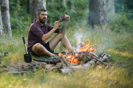 Man lumberjack with beard sharpen axe at bonfire in forest on natural landscape. Logging and chopping concept. 스톡 콘텐츠