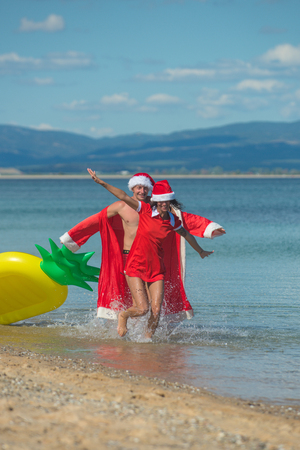 Winter holiday and vacation. Xmas party celebration and activity. Christmas couple with pineapple inflatable mattress. Couple in love of happy man and woman in water. New year girl and guy as santa. Stock Photo