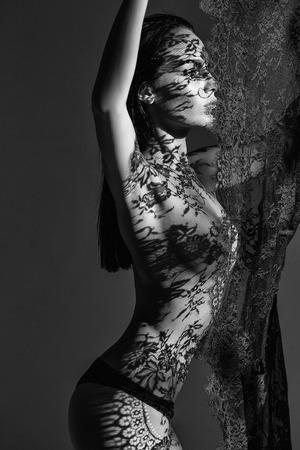 hübsches nacktes Mädchen oder süße Frau mit langen brünetten Haaren in modischen schwarzen Höschen hält Spitze auf dunklem Hintergrund, hat sexy Körper und nackte Brust