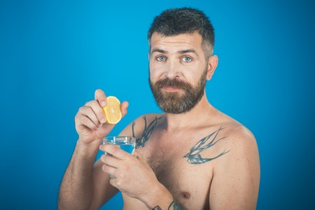 Man with long beard hold water glass on blue background. Hipster drink clean healthy water with lemon, refreshing. Health and dieting. Lemon natural juice, vitamin. Life source and healthcare. Imagens