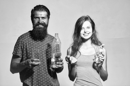 Smiling couple of beautiful long-haired girl and handsome bearded man hold water bottles apple and glass on grey wall