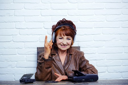 Spy and operator. Old woman with cassette recorder listen music in headphones. Old school music player, radio. Audio book and new technology, education. happy granny dj in headset with cassette player