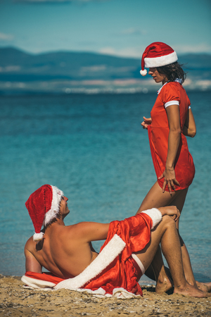 Winter holiday and vacation. New year girl and guy as santa. Couple in love of happy man and woman in water. Xmas party celebration and activity. Christmas couple in red at beach.