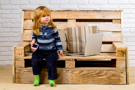 Kid at computer with cell phone, sms and 4G. Social network and new technology. School and communication. child with laptop and mobile phone, education. Small boy blogging on bench, online buy. Stock Photo