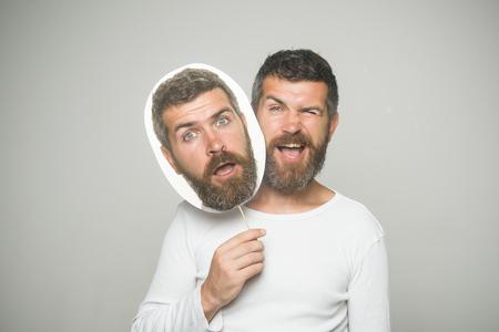 Hipster met knipogen en verrast gezicht houden portret naamplaatje. Man of bebaarde man op grijze achtergrond. Gevoel en emoties. Kapper mode en schoonheid. Man met lange baard en snor. Stockfoto