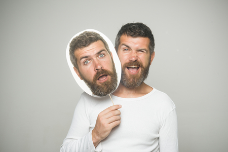 Hipster with winking and surprised face hold portrait nameplate. Guy or bearded man on grey background. Feeling and emotions. Barber fashion and beauty. Man with long beard and mustache.