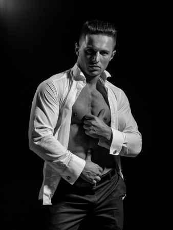 young handsome gentleman undressing fashion white shirt with sexy bare muscular torso in studio
