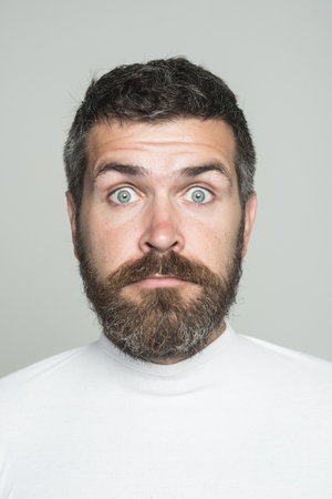 Man with long beard and mustache. Guy or bearded man on grey background. Barber fashion and beauty. Feeling and emotions. Hipster with surprised face.