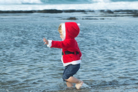 Cute baby boy in red santa coat with hood and wet shorts walks barefoot in blue sea water on beach on sunny summer day on natural background