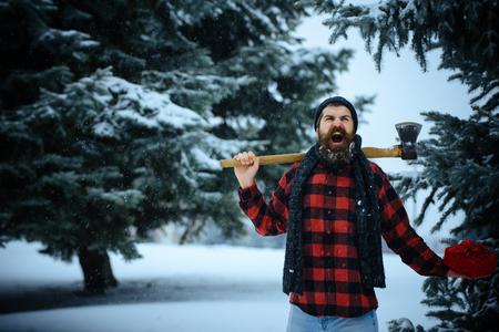 나무에 도끼와 크리스마스 hipster 등심입니다. 크리스마스 방황, 하이킹, 여행. 선물 상자가 눈 감기 숲에 새 해 남자. 겨울 휴가 축하. 도끼와 겨울 숲에 스톡 콘텐츠