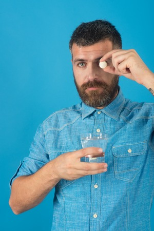 man drink medical pill with water on blue background, healthcare and life source, painkiller and headache, flu and cold