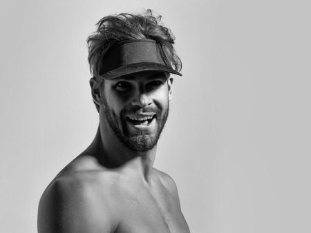 Joyful handsome man sexy young bearded male model with beard in red cap peak visor topless with nude torso and sexi body smiles on grey background Stock Photo