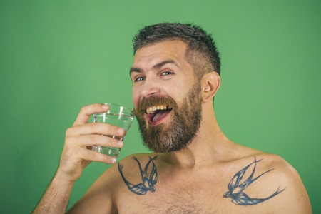 Happy hipster drink clean healthy water, refreshing. Health and dieting. Hangover and thirst. Life source and healthcare. Man with long beard hold water glass on green background. Imagens - 91102077