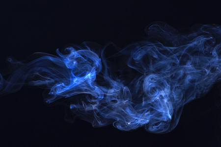 Spirit and ghost, miracle. Smoking cloud backdrop. Blue ink in freeze motion, powder splatted explosion. Blue smoke on black background. Abstract background with smoke.