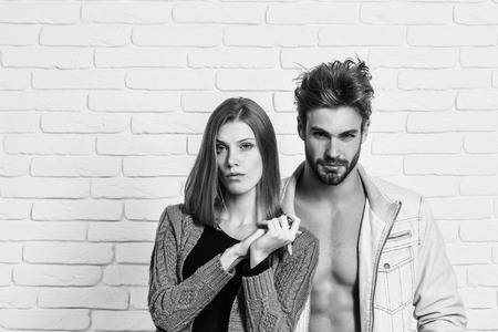 Young couple of handsome man or muscular macho in unzipped jacket with pretty cute girl or beautiful woman in knitted coat on white brick background Stock Photo - 91679137