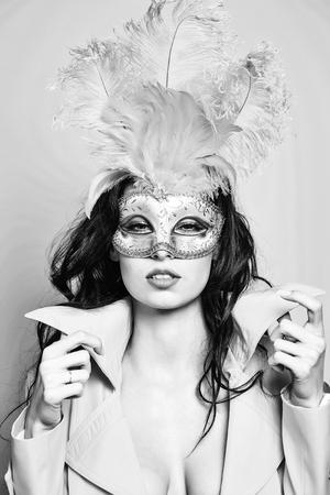 Het mooie meisje of de leuke sexy vrouw heeft donkerbruin haar in gouden feestelijk Carnaval-masker met veren en gele laag op oranje achtergrond
