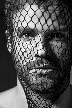 Young man blond bearded male with beard or robber bandit gangster wears mask of black fishnet stocking on face on dark background