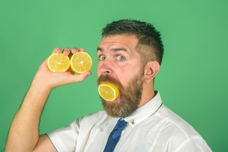 Dieting and fitness. Man with long beard eat lemon. Vitamin citrus at hipster on green background. Fruit and healthy organic food. Vegetarian, health and wellbeing. Stock Photo