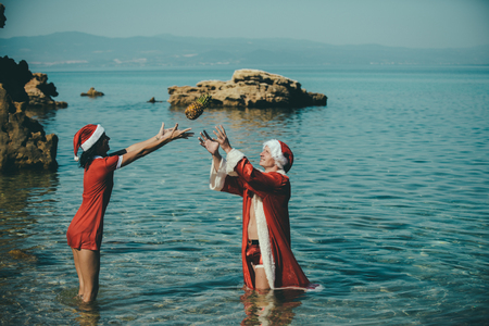 Couple in love of happy man and woman in water. Xmas party celebration and activity. New year girl and guy as red santa claus. Winter holiday and vacation. Christmas couple throw pineapple at beach.