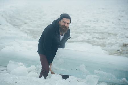 Cold weather and ice age. Power and strength of man with frozen hummock. Man with beard hold big ice block. Cracked ice at Hercules guy in Christmas. Winter holiday and activity.