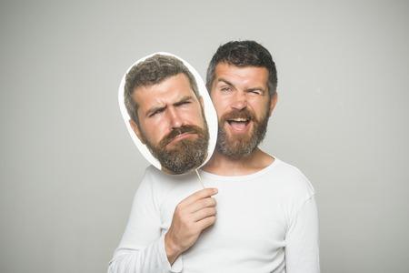 Man of bebaarde man op grijze achtergrond. Hipster met knipogen en droevig gezicht houdt portret naamplaatje. Man met lange baard en snor. Kapper mode en schoonheid. Gevoel en emoties.