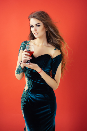 Woman holding glass of wine. Girl in blue evening dress. Model with long brunette hair and makeup on red background. Holiday celebration concept. Fashion and beauty salon.