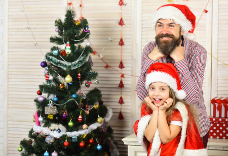 Happy family celebrate new year and Christmas. Father and child embrace. Father and daughter in santa hat at Christmas tree. Xmas party celebration. Winter holiday and New year. Stock Photo