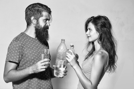 Attractive couple of beautiful long-haired girl and handsome bearded man with water bottles glass and apple look at each other on grey wall Stock Photo