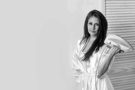 pretty girl or beautiful woman, housewife, with long brunette hair in sexy dressing gown with electric iron in hand indoors on white wall background. Housework and housekeeping, copy space