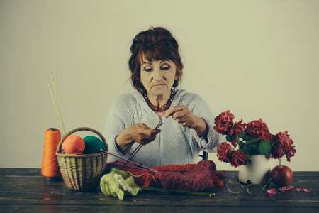 Granny character at Christmas eve or womens day. Needlework and knitting hobby. Old woman knitting socks from colorful thread. Old lady or grandmother with needle and yarn. Pension and retirement, old age. Stock Photo