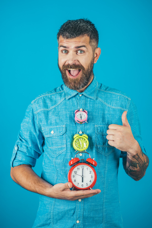 Time and perfect morning. Overtime and urgency. Time management and countdown. Lifetime, business and deadline. happy man with beard hold alarm clock show thumb up gesture, watchmaker