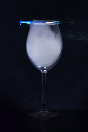drug and unhealthy lifestyle, glass with blue smoke and medical syringe on black background, bad habits and addiction, health and medicine, morphine, alcoholism