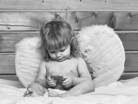 Mignon heureux beau garçon espiègle enfant avec les cheveux mouillés, assis dans la serviette de bain blanc bain moelleux nu intérieur sur fond en bois dans les ailes d'ange à plumes jouant sur le téléphone mobile, photo horizontale Banque d'images - 91826482