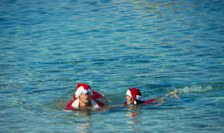 Xmas party celebration and activity. Christmas couple in red at beach. New year girl and guy as santa. Couple in love of happy man and woman in water. Winter holiday and vacation. Stock Photo