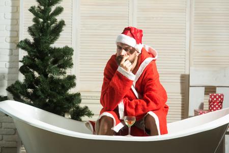 Christmas man with beard, waiting. Hipster santa at Christmas tree drink wine, loneliness. Expectation, love and betrayal. Winter holiday and xmas party. Home alone, bad santa in bath.