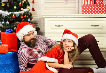 Happy family celebrate new year and Christmas. Father and child at present box. Father and daughter in santa hat at Christmas tree. Xmas party celebration. Winter holiday and New year. Stock Photo