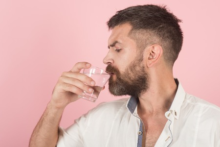 Hipster drink clean healthy water, refreshing. Health and dieting. Life source and healthcare. Hangover and thirst. Man with long beard hold water glass on pink background.
