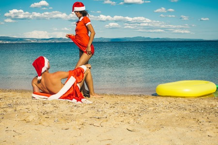 Couple in love of happy man and woman in water. New year girl and guy as santa. Xmas party celebration and activity. Winter holiday and vacation. Christmas couple with pineapple inflatable mattress.
