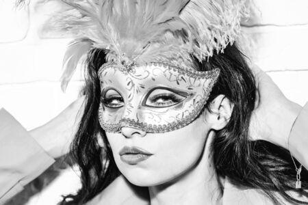 Het mooie meisje of de leuke sexy vrouw heeft donkerbruin haar in gouden feestelijk Carnaval-masker met veren en gele laag op witte bakstenen muurachtergrond