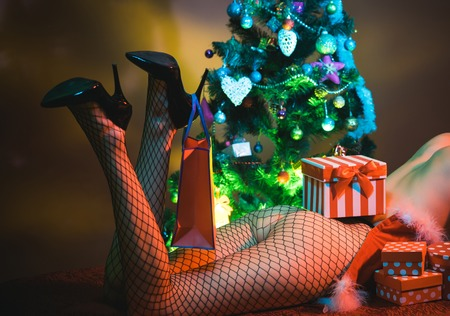 Christmas party and sex games. Young woman with legs in tights, present for boys. Call girl or sexy woman at xmas. New year strip and gift for adult. shopping bag on sexy female legs with buttocks.