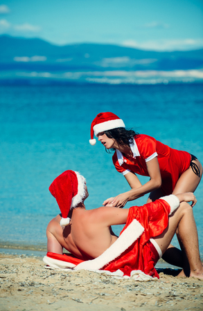 New year girl and guy as santa. Couple in love of happy man and woman in water.