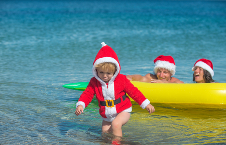 New year man, girl with small boy. Winter holiday vacation. Santa child, parents at Christmas.n water.
