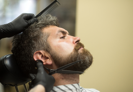 Haircut of bearded man, archaism. Barber and hairdresser, future. Fashion and beauty, innovation. Man cut long beard and mustache with scissors. Hipster with serious face in barbershop, new technology.