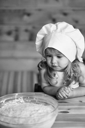 Kleines nettes Baby oder Kind mit glücklichem Gesicht in der weißen Kochuniform mit Chefhut und -schürze, die Teig mit Mehl in der Glasschüssel in der Küche auf hölzernem oder Holzhintergrund knetet Standard-Bild - 91602262