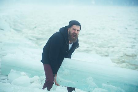 冬の休日と活動。あごひげを生やした男は大きな氷の塊を持っている。クリスマスにヘラクレスの男に氷が割れた冷凍ハンモックを持つ人間の力と