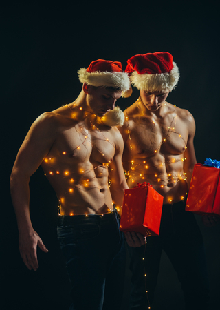 New year strip and gifts for adults. Twins santa with muscular body in garland. Christmas party and games. Young men in santa costume, present for girls. Call boys or athlete men at xmas.