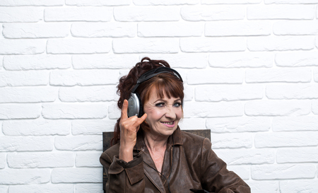 old woman listen music in headphones on brick wall background, happy granny, audio book, new technology, old school music and radio operator
