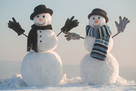 christmas snowman couple of spy agent or gentleman, businessman in hat, gloves and scarf on blue sky, winter holiday celebration, new year and xmas, winter fashion