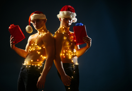 Call boys or sexy athlete men at xmas. Christmas party and sex games. Twins santa with muscular body in garland. Young men in santa costume, present for girls. New year strip and gifts for adults. Stock Photo
